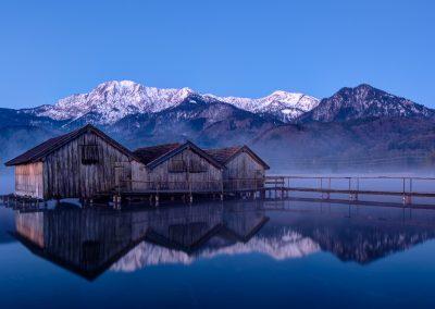 Spiegelung der 3 Bootshäuser am See